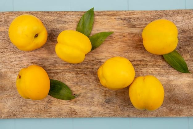 Вид сверху свежих желтых персиков с листьями, изолированными на деревянной кухонной доске на синем фоне