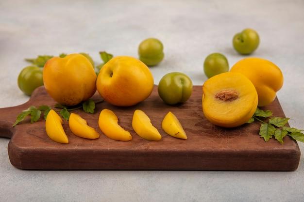 Вид сверху свежих желтых персиков с дольками на деревянной кухонной доске с зелеными алычами, изолированными на белом фоне