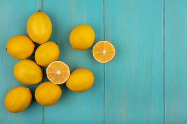 Вид сверху свежих лимонов с желтой кожурой, изолированных на синем деревянном фоне с копией пространства
