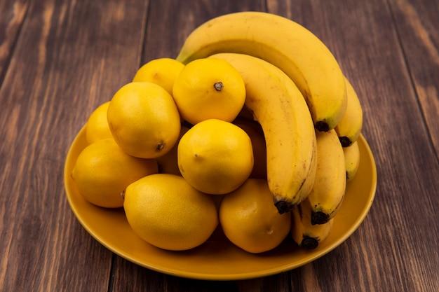 木製の表面にバナナと黄色のプレート上の新鮮な黄色の皮を剥がれたレモンの上面図