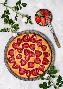 Вид сверху свежеиспеченного творожного торта с клубникой на светло-сером фоне. концепция вкусной домашней сладкой еды. скопируйте пространство.
