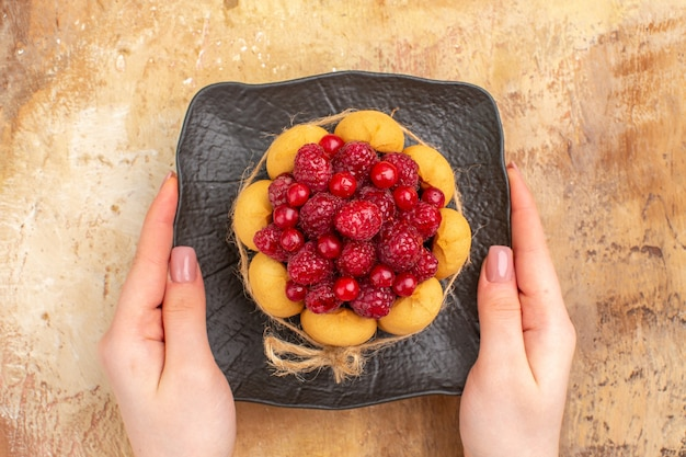 혼합 색상 배경에 갈색 접시에 갓 구운 선물 케이크의 상위 뷰