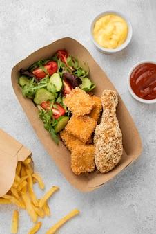 Вид сверху жареных куриных наггетсов и картофеля фри с соусами