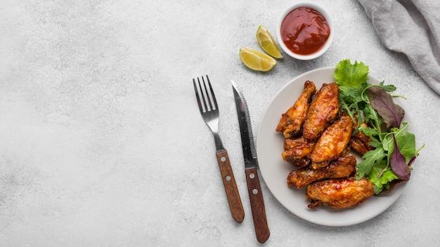 Вид сверху жареной курицы на тарелке с салатом и соусом