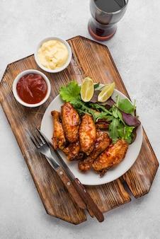 Вид сверху жареной курицы на тарелке с соусом и газированным напитком