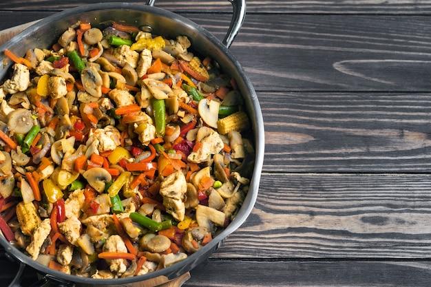 Вид сверху жареной курицы со смесью овощей на сковороде на деревянном столе