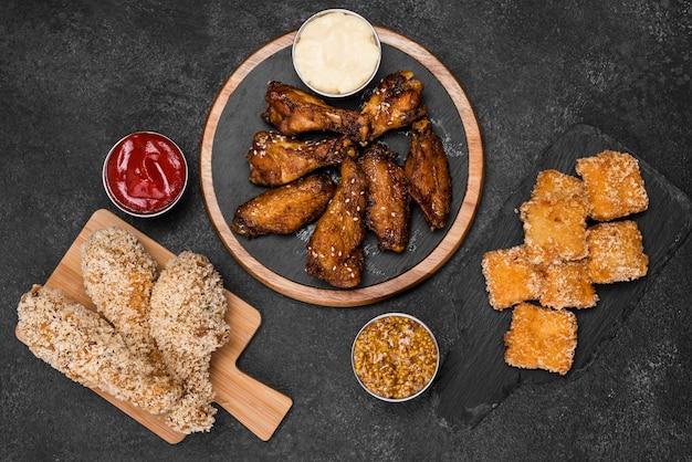 Вид сверху жареной курицы с наггетсами и соусом