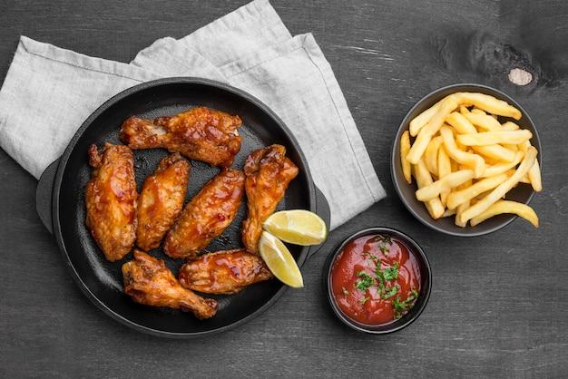 Вид сверху жареной курицы с соусом и картофелем фри