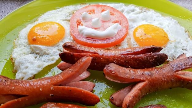 아기를 위한 아침 식사를 제공하는 녹색 접시에 계란 프라이와 소시지의 최고 전망.