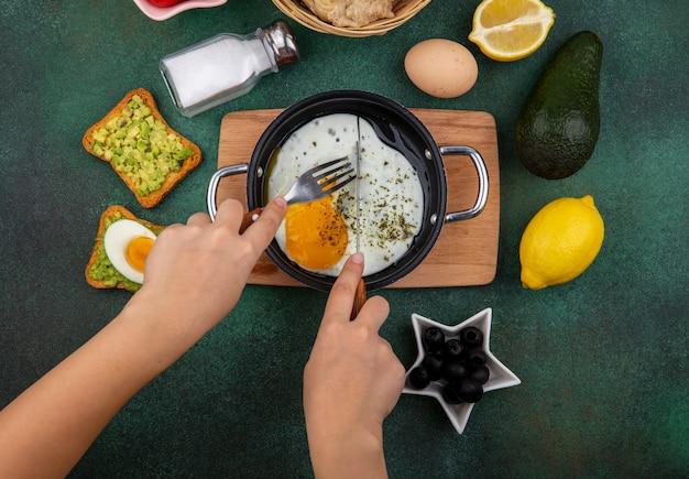 Вид сверху жареного яйца на сковороде на деревянной кухонной доске с поджаренными ломтиками хлеба с мякотью авокадо, черными оливками на зеленом
