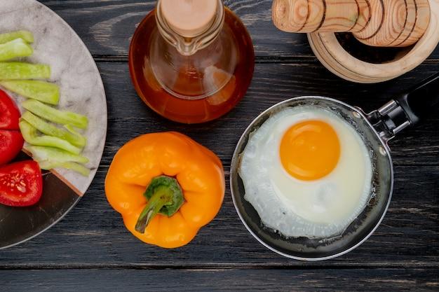 Вид сверху жареного яйца на сковороде с перцем оранжевая с яблочным уксусом на деревянном фоне