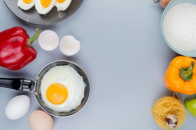 Вид сверху жареного яйца на сковороде с яичной скорлупой на сером фоне с копией пространства