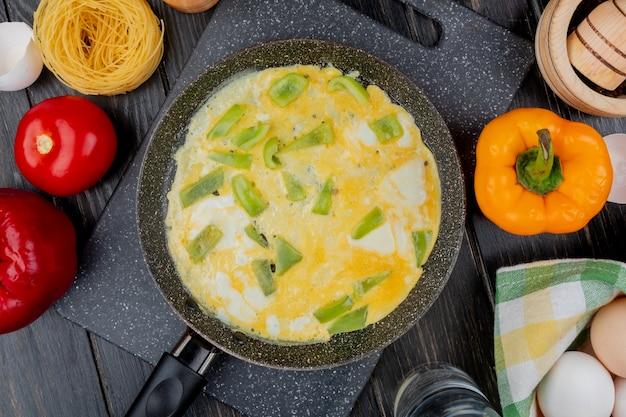 Вид сверху жареного яйца на сковороде с разноцветным болгарским перцем с помидором на деревянном фоне