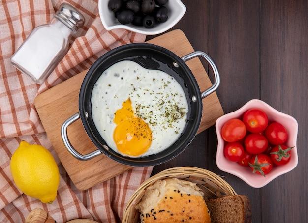 木のチェッククロスにブラックオリーブチェリートマトと木製キッチンボード上のフライパンの卵の平面図