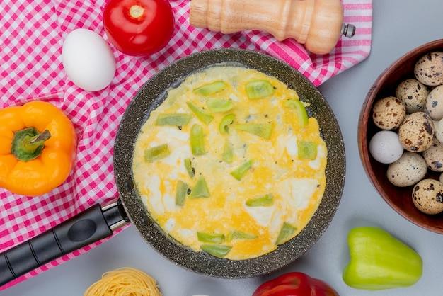 白い背景の上の木製のボウルにウズラの卵とピーマンとフライパンで目玉焼きのトップビュー
