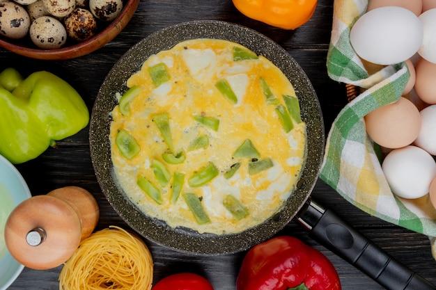 木製の背景に新鮮な鶏の卵とフライパンでみじん切りピーマンのスライスと目玉焼きの平面図