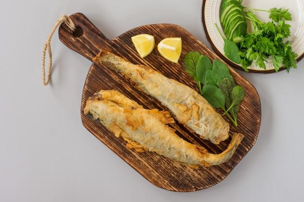 Взгляд сверху наваги жареной рыбы служил на деревянной разделочной доске с лимоном, овощами и зеленью на сером фоне.