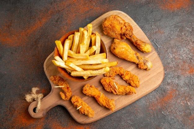 Вид сверху жареного картофеля и курицы на деревянной разделочной доске