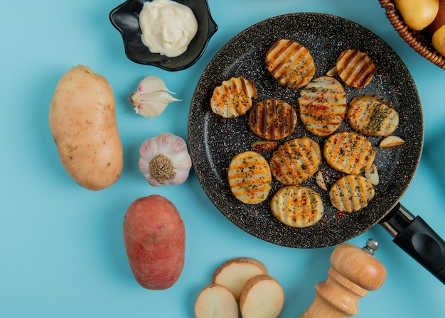Вид сверху ломтики жареного картофеля в сковороде с сырой одной майонезно-чесночной солью на синем