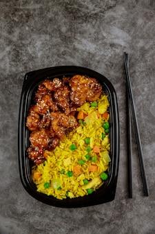 젓가락으로 볶음밥과 치킨 데리야끼의 상위 뷰. 건강한 음식.