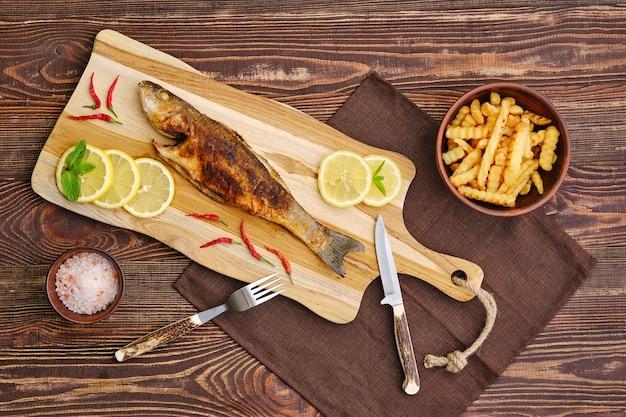 나무 커팅 보드에 튀긴 감자와 튀긴 농어의 상위 뷰