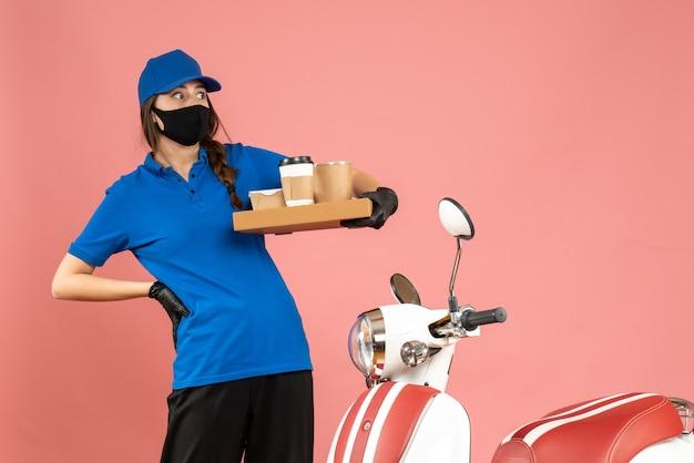 パステル ピーチ色の背景にコーヒーの小さなケーキを保持しているオートバイの隣に立っている医療マスク手袋を着て、おびえた宅配便の女の子のトップ ビュー