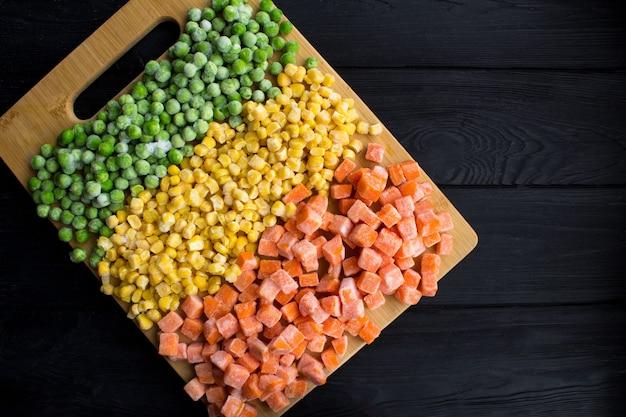 Вид сверху замороженных овощей на коричневой разделочной доске