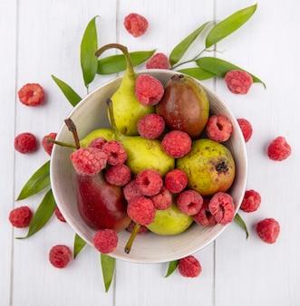 Вид сверху на миску с фруктами и листьями на деревянной поверхности