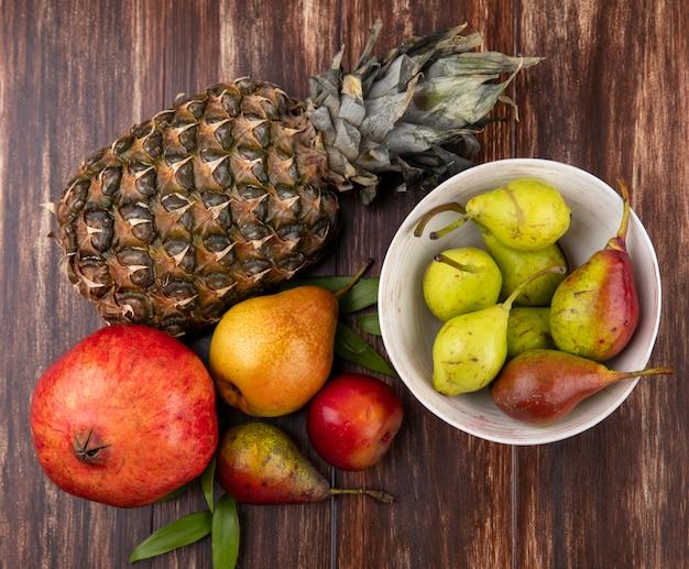 Вид сверху на фрукты и миску персика на деревянной поверхности