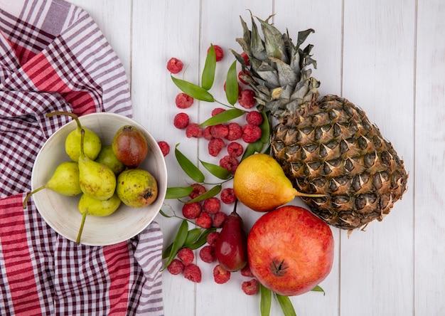Вид сверху на фрукты и миску груш на клетчатой ткани с листьями на деревянной поверхности