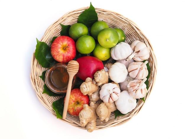 果物と野菜の白い背景で隔離の手に蜂蜜健康食品と竹かごのセットのトップビュー