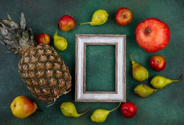 Вид сверху фруктов вокруг рамки на зеленой поверхности