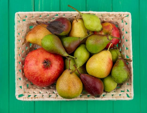 Вид сверху на фрукты, такие как яблоко, гранат, груши и персик в корзине на зеленой поверхности