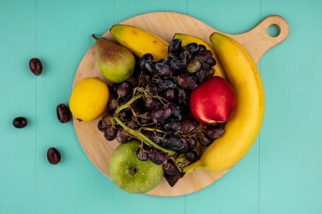 Вид сверху на фрукты как банан, яблоко, лимон, виноград, персик, груша на разделочной доске на синем фоне