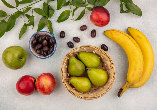 Вид сверху на фрукты в виде корзины и миски из груши и винограда с бананом, яблоком, персиком с листьями на белом фоне