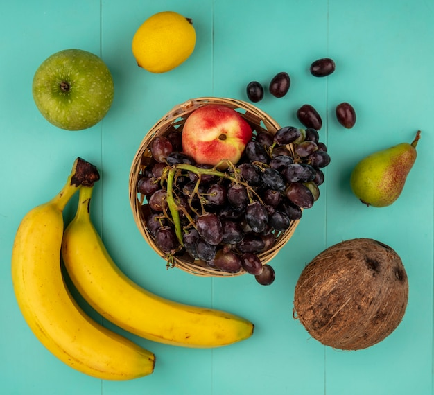青い背景にバナナアップルレモン梨ココナッツとブドウと桃のバスケットとして果物の上面図
