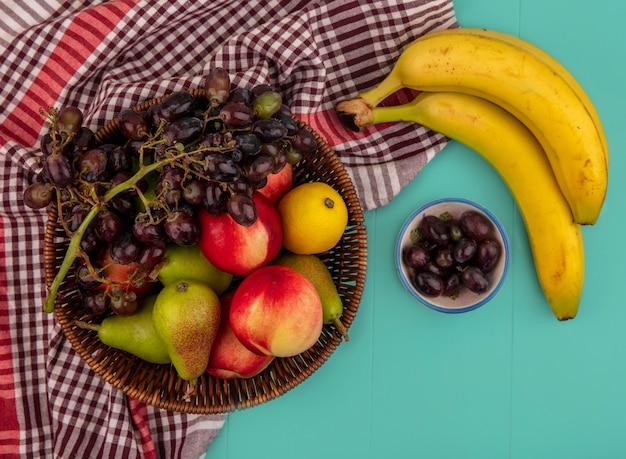 Вид сверху на фрукты в виде корзины с виноградной грушей, персиком, яблоком и лимоном на клетчатой ткани с бананами и виноградными ягодами на синем фоне