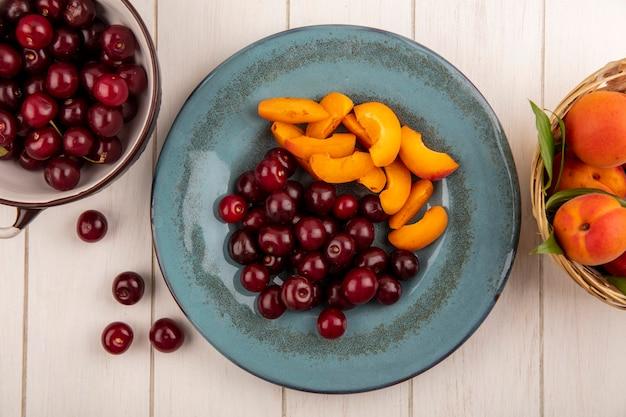 木製の背景にさくらんぼのボウルとアプリコットのプレートとバスケットのさくらんぼとアプリコットスライスとしての果物の上面図