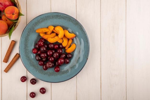 Вид сверху на фрукты в виде вишни и кусочков абрикоса в тарелке и корзине абрикосов с корицей на деревянном фоне с копией пространства