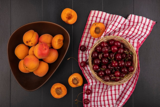 Вид сверху на фрукты в виде вишен и абрикосов в миске и корзине, на клетчатой ткани и черном фоне