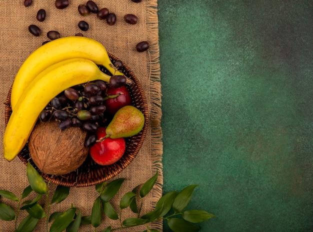 Вид сверху на фрукты как кокос, банан, виноград, груша, персик в корзине с листьями на мешковине на зеленом фоне с копией пространства