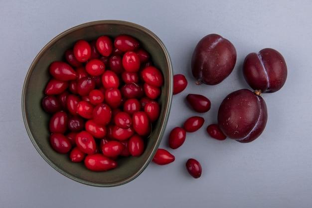 Вид сверху на фрукты в виде ягод кизила в миске и плюотов на сером фоне