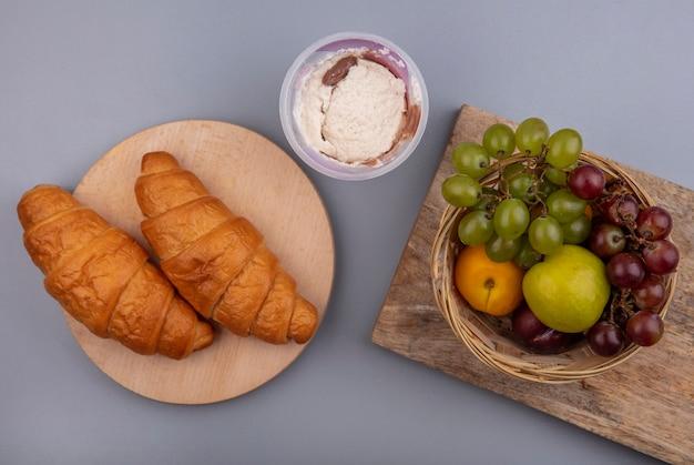 Вид сверху на фрукты в виде виноградного нектакота в корзине с круассанами на разделочных досках на сером фоне