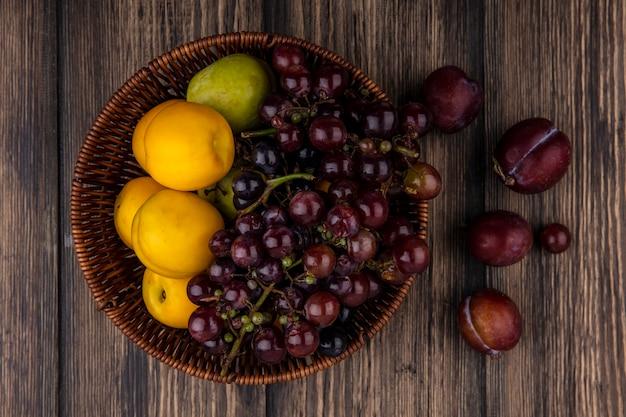 バスケットのブドウプルオットネクタコットと木製の背景のフレーバーキングプルオットとしての果物の上面図