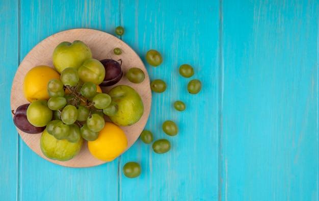 Вид сверху на фрукты в виде нектакотов сливы и сливы на разделочной доске и виноградных ягодах на синем фоне с копией пространства