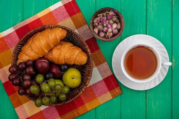ブドウのプルオットとしての果物の上面図格子縞の布の上にバスケットにクロワッサンと花のボウルと緑の背景にお茶のカップと花のボウル