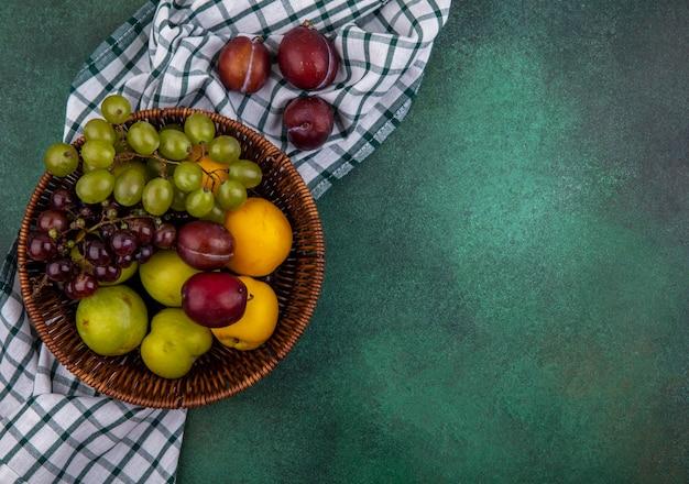 コピースペースと緑の背景に格子縞の布の上のブドウのプルオットとバスケットのネクタコットとして果物の上面図