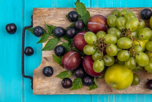 Вид сверху на фрукты в виде гроздей винограда с виноградными ягодами и листьями на разделочной доске на синем фоне