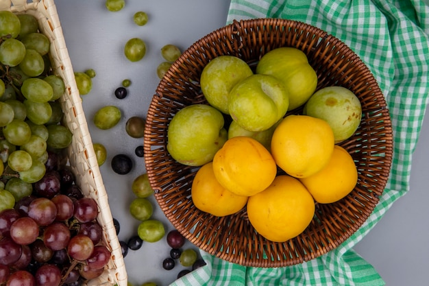 格子縞の布の上のバスケットと灰色の背景にブドウの果実とブドウのバスケットの緑のプルオットとネクタコットとしての果物の上面図