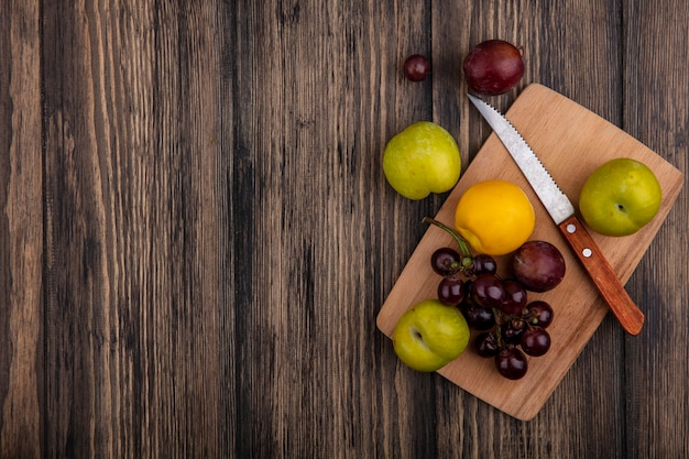 ネクタコットグリーンとフレーバーキングプルオットブドウとしての果物の上面図コピースペースと木製の背景のまな板にナイフでブドウ